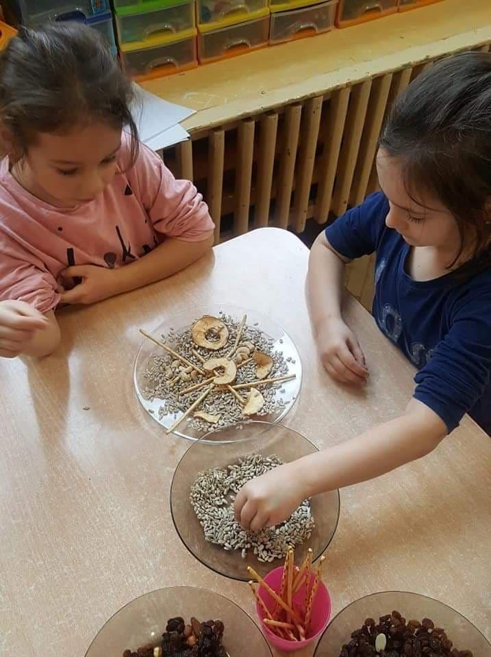 Na zdjęciu dziewczynki tworzą mandalę z produktów spożywczych